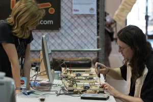Super Awesome Sylvia watches Evil Mad Scientist's Windell Oskay adjust a WaterColorBot before Maker Faire opens.